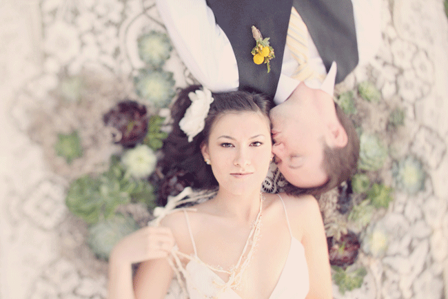 overhead shot of groom kissing bride as both lay down on ground