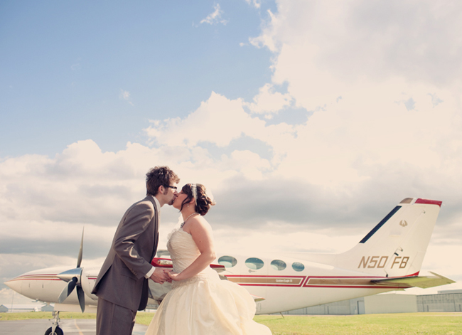 Bride and groom kiss in front of airplane at Wiley Post Airport