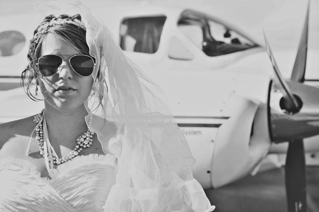 black and white photo of bride in aviator sunglasses beside prop plane