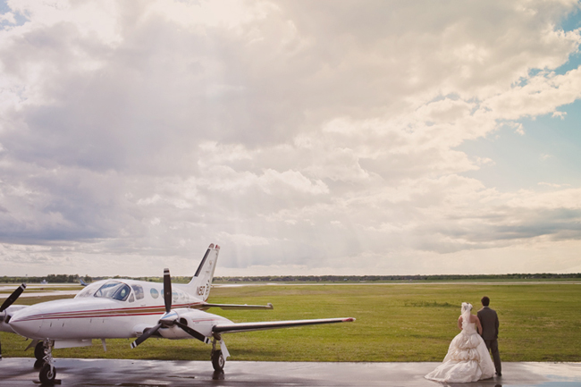 bride and groom on tarmac next to prop plane