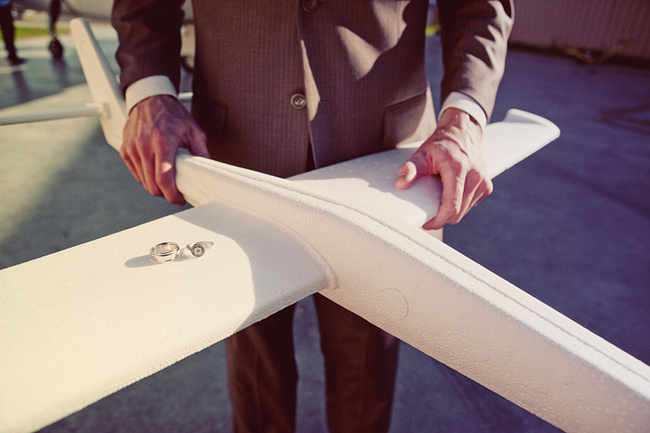 groom holds model white airplane with rings sitting on one wing