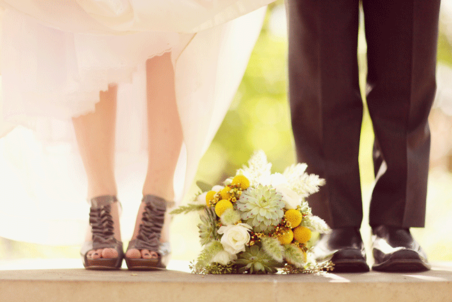 bouquet laying on the ground between bride and grooms feet