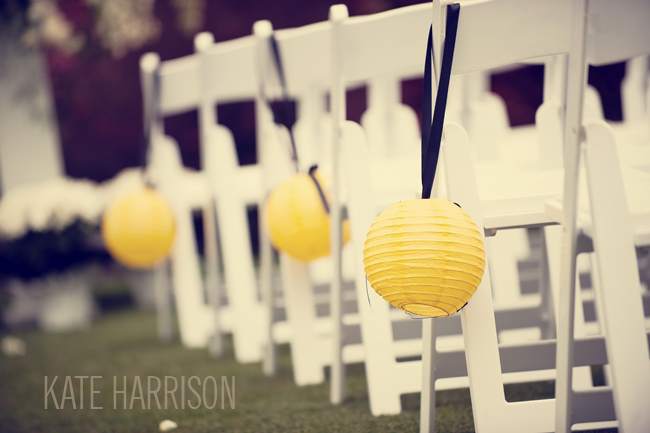 Paper lanterns in a sunny yellow color hang as aisle markers on white folding chairs
