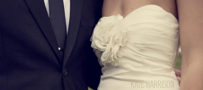 Bride's gorgeous dress and groom in black tie and tuxedo