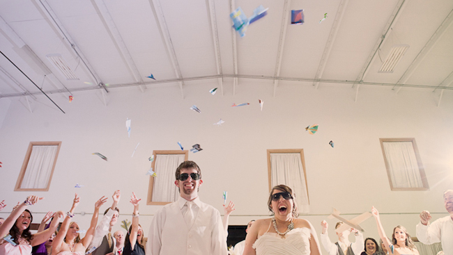 guests throw paper aiplanes at newlyweds