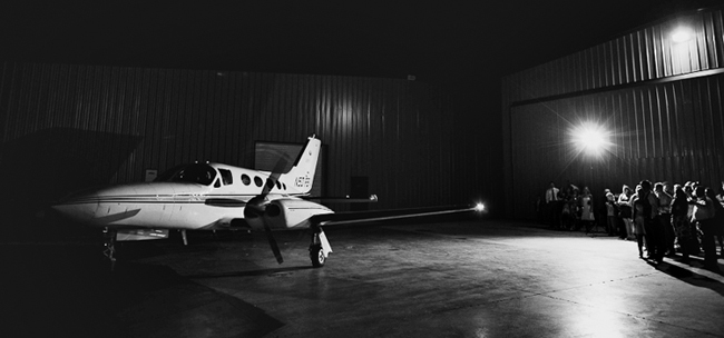 black and white photo of airplane with guests in background