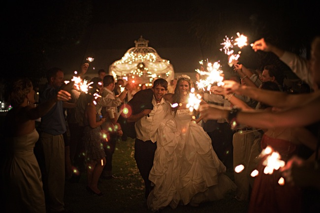 bride and groom escorted through archway of sparklers