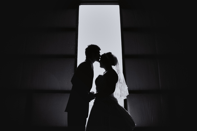 black and white photo of newlyweds in airplane hanger doorway