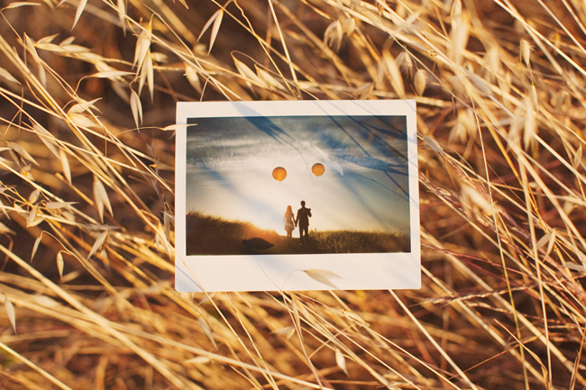 polaroid photo laying on grass of couple with yellow balloons at sunset
