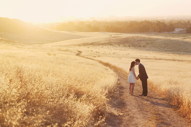 Kissing on the dirt path overlooking valley with sunlight behind