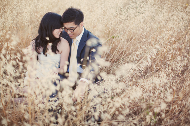 couple sit together amidst tall grass