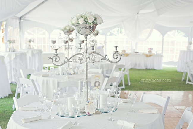 white outdoor tents, large silver candelabra in centre of table