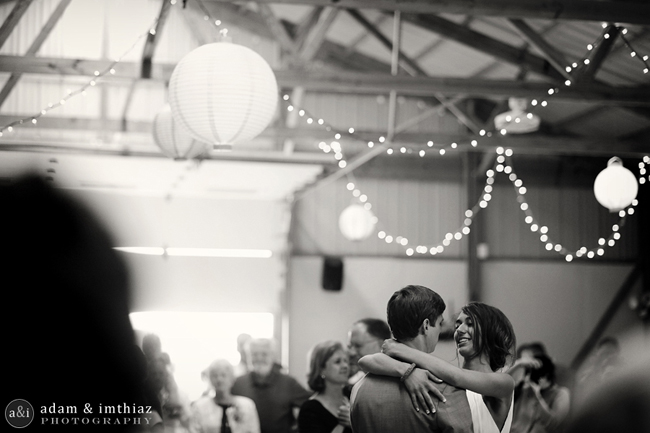 black and white photo guests and newlywed couple dancing in barn