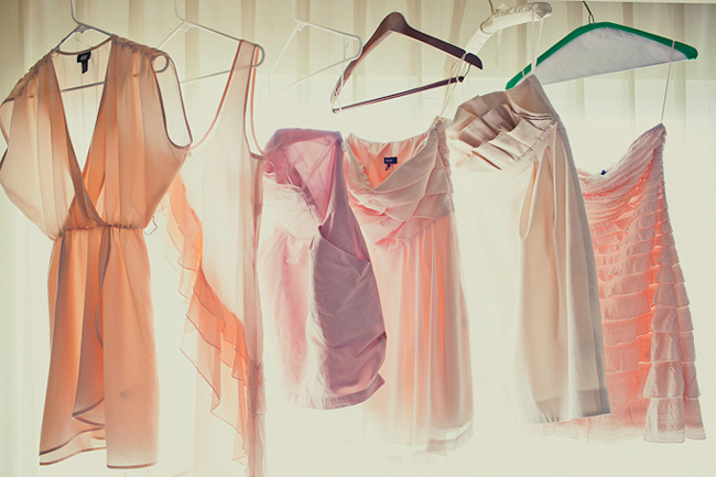 pastel color mismatched bridesmaid dresses hanging in window sunlight