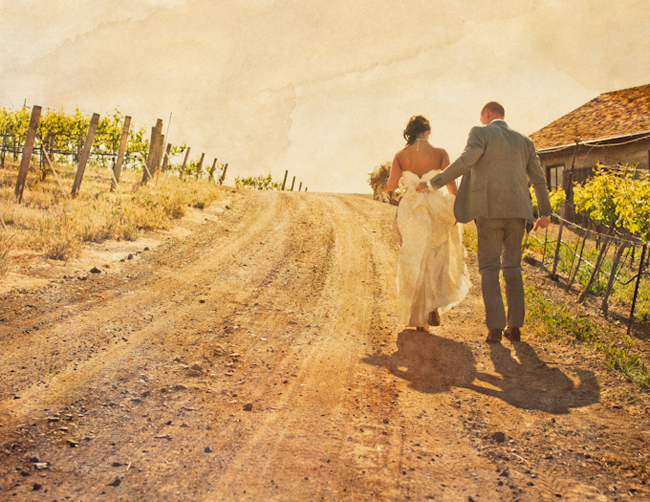 sunlight capturing bride and groom walking up dirt path among vineyard