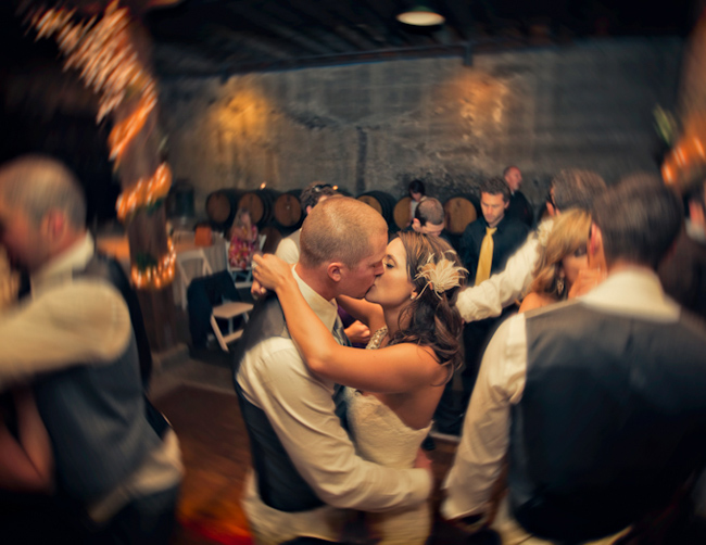 bride and groom kiss on dance floor in cellar of Murrieta's Well Winery