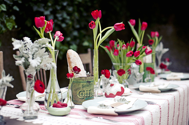 table with red tulips in vases, coffee tins filled with fresh French bread