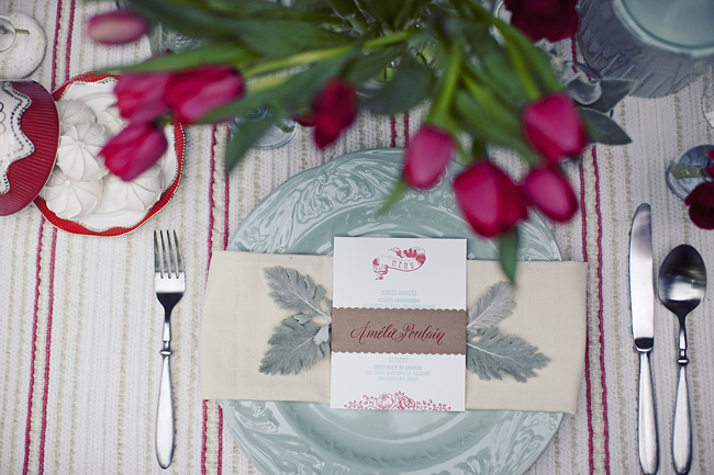 place setting with dusty miller leaves under menu and French country-style plates