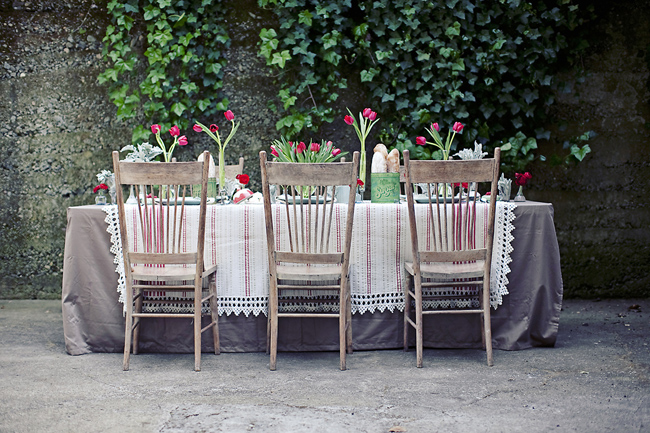 table, oak chairs, red tulips in vases, coffee tins filled with fresh French bread