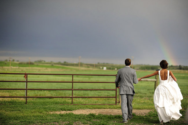 Brooke and Seth walk towards a rainbow amid gray skies