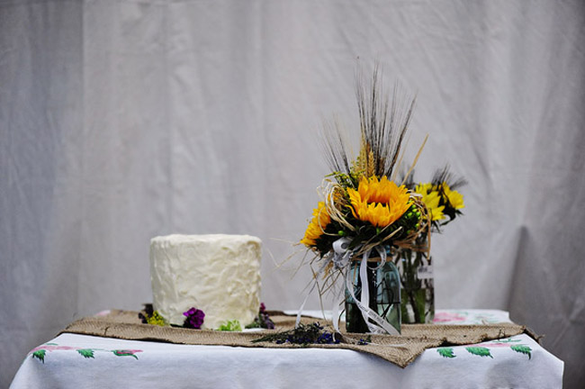 sunflowers in mason jars next to wedding cake