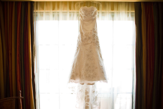 bridal dress hanging in front of window