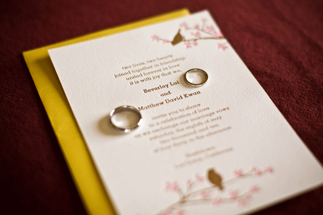 wedding bands lay on wedding invitation