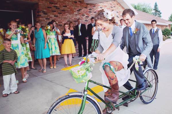 bride and groom riding away on their bicycle