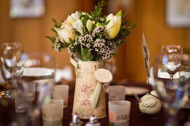 watering can with flowers as centerpiece