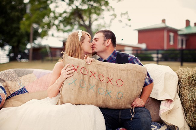 bride and groom hold burlap sack with X's and O's, The Inn at Fairfield Farm in background