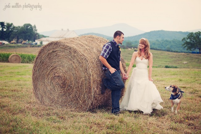 bride and groom stand next to hay bale with their dog