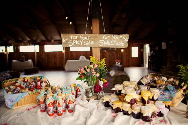 Bottles of hot sauce and homemade jam sit on wedding favor table
