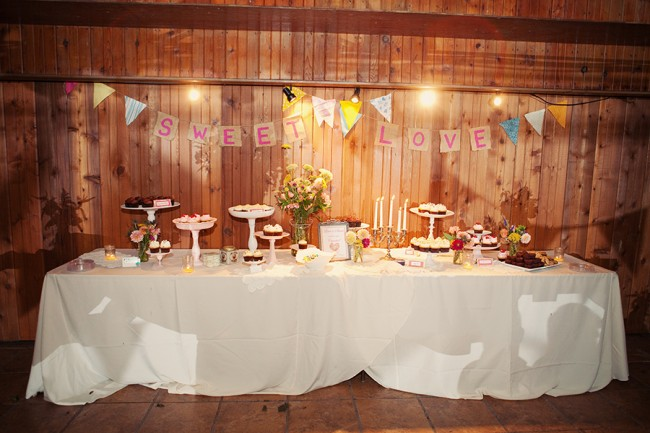 "photo of dessert table inside against wood panels, burlap bunting reads, ""Sweet Love"""