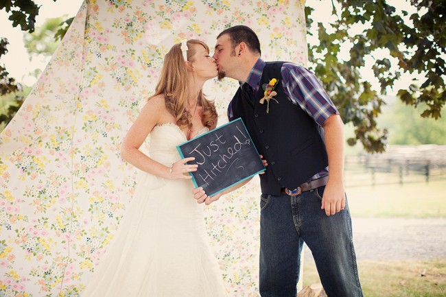 "Bride and groom kiss in front of flower sheet and hold chalkboard sign that says, ""Just Married!"""