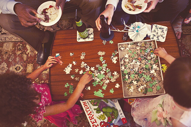 overhead photo of guests making a puzzle, drinking beer and eating cake