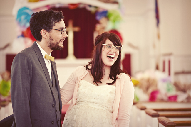 bride and groom laughing with colorful decor at church