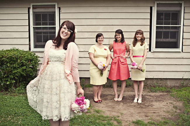 Bride in a pink cardigan with bridemaids in mismatched dresses behind her