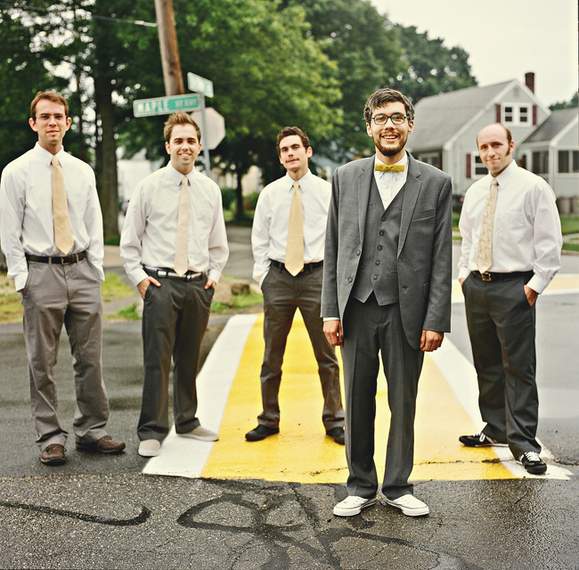 Groom in gray suit and yellow bow tie stands with groomsmen on street