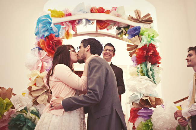 bride and groom kiss under multi color tissue paper alter