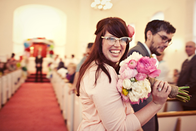 Bride holds up bouquet of peonies and ranunculus