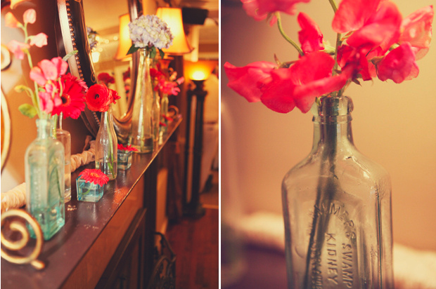 Vases and red flowers lined up on mantle with mirror in the middle