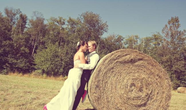 bride and groom lean against hay bale in field