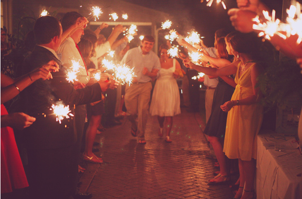 bride and groom walk underneath a sparkler send off