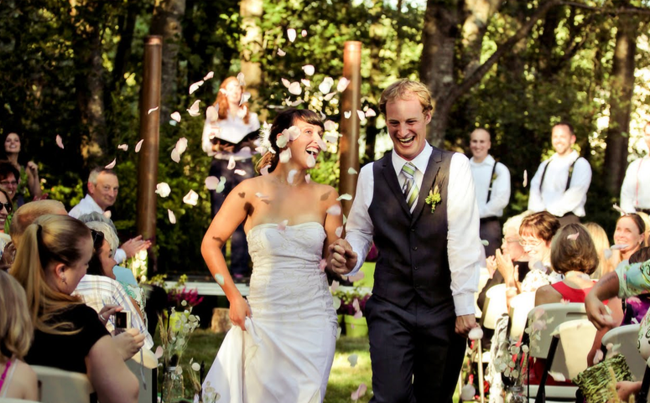 wooded backyard wedding recessional with rose petals