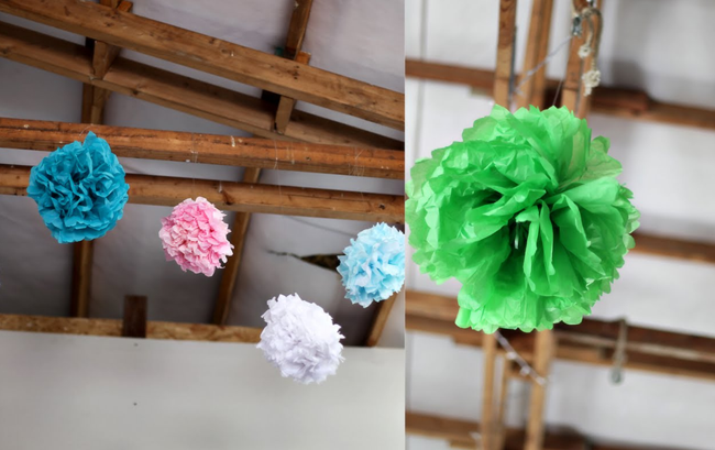 blue, pink, white, and green pom-poms hang from wood beams