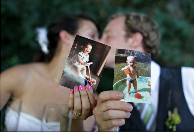 bride and groom hold pictures of when they were children