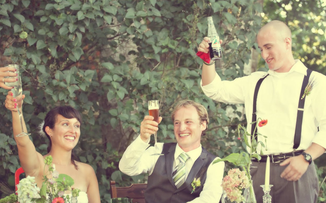 bride and groom raise their glasses along with the best man
