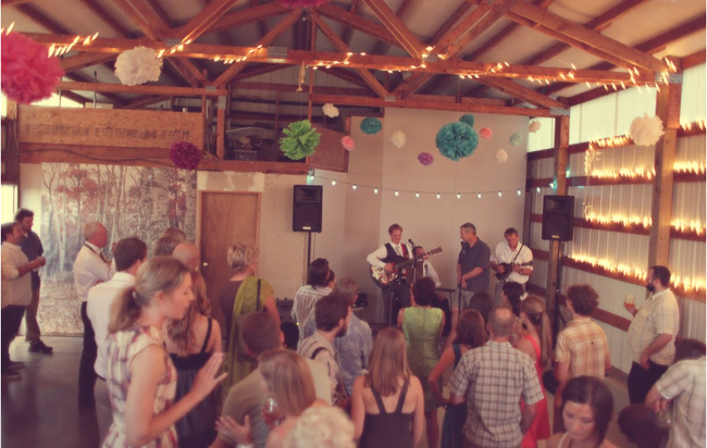 band playing inside the barn as guests dance