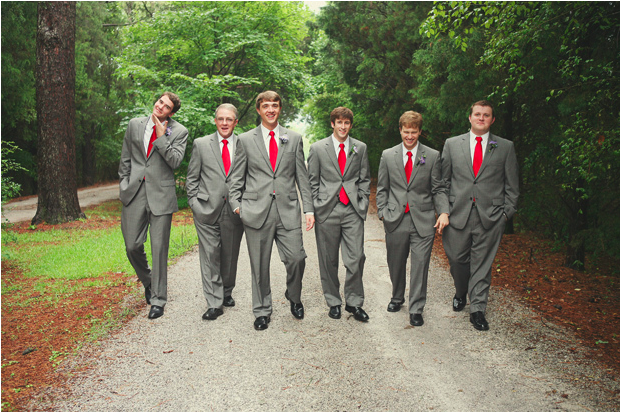 Groom and groomsmen dressed in gray suits with bright red neckties