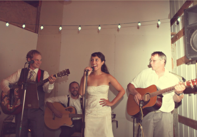 bride singing with groom playing guitar on mini stage inside barn